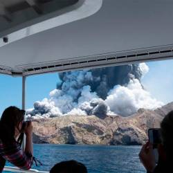 This handout photograph courtesy of Michael Schade shows the volcano on New Zealand's White Island spewing steam and ash moments after it erupted on Dec 9. — AFP
