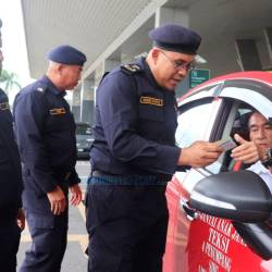 Mohd Syafiq checks the licences of a taxi driver, who is also an e-hailing driver the operation at Sibu Airport. — TheBorneoPost