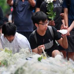 Mourners place flowers and say prayers at the site where a protester died the day before, prior to the start of a new rally in Hong Kong on June 16, 2019. — AFP