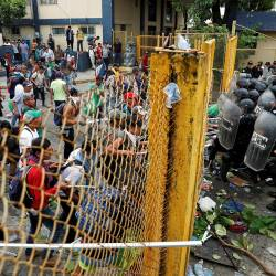 Men, part of a caravan of thousands of migrants from Central America en route to the US, push the border gate as they try to cross into Mexico and carry on their journey, in Tecun Uman, Guatemala, Oct 28, 2018. — Reuters