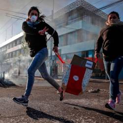 A looter flashes the V sign as she runs during protests in Valparaiso, Chile, on Oct 20, 2019. — AFP