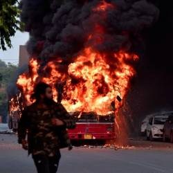 A man walks on a street as a bus is on fire following demonstration against the Indian government's Citizenship Amendment Bill (CAB) in New Delhi on Dec 15. — AFP