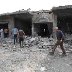 People walk past destruction at the scene of an area targeted by regime airstrikes in the village of Kafr Aweid in which five people were killed, including two children on June 5, 2019 in the Syria's northern Idlib province. - AFP