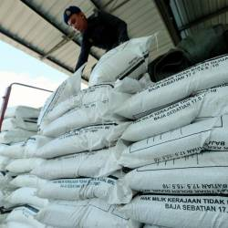 A Domestic Trade and Consumer Affairs Ministry officer examines subsidised paddy fertiliser believed to have been misappropriated at a factory in Sedaka, Yan on June 24, 2019. — BBX