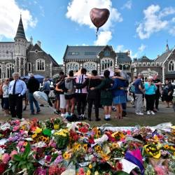 A group of students (C) sings in front of flowers left in tribute to victims at the Botanical Garden in Christchurch on March 19, 2019, four days after a shooting incident at two mosques that claimed the lives of 50 people. — AFP