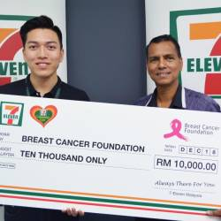 Communications and Creative Manager (Marketing) of 7-Eleven Malaysia, Lawrence Ng (left), presenting a mock cheque to Razlan.