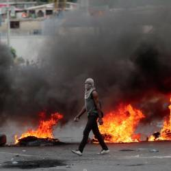 A demonstrator walks past a burning barricade during anti-government protests in Port-au-Prince, Haiti, on Feb 15, 2019. — Reuters