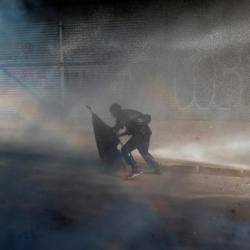 A demonstrator is sprayed by security forces with a water cannon during a protest against Chile's government in Santiago, Chile, Nov 14. — Reuters