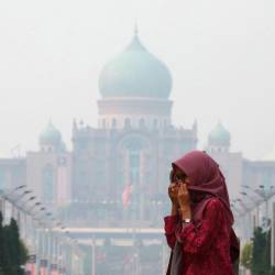 A woman covers her face with a scarf in front of the Malaysia's Prime Minister's office, which is shrouded in haze, in Putrajaya, Malaysia, September 17, 2019. - Reuters