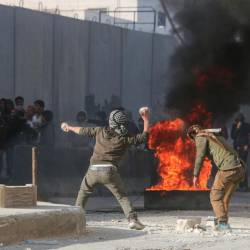 Syrian protesters hurl stones amid clashes with Turkish forces following a demonstration against Turkey's presence in northern Syria on Nov 17 in the town of al-Bab in Syria's northern Aleppo governorate. — AFP