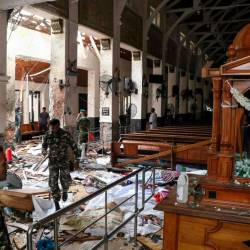 Sri Lankan security personnel walk past dead bodies covered with blankets amid blast debris at St. Anthony's Shrine following an explosion in the church in Kochchikade in Colombo on April 21, 2019. — AFP