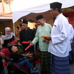 Prime Minister Tun Dr Mahathir Mohamad hands over donations to special needs children at a breaking-of-fast and welfare event at Masjid Nurus Salam, Kampung Ewa in Langkawi tonight. - Bernama