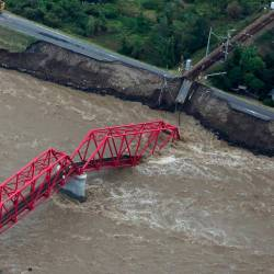 This aerial view shows a damaged train bridge over the swollen Chikuma river in the aftermath of Typhoon Hagibis in Ueda, Nagano prefecture on Oct 13, 2019. — AFP