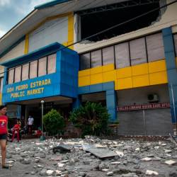 A resident walks past debris from a partially damaged building after a 6.4 magnitude earthquake hit the night before in the city of Digos, Davao del Sur province on the southern Philippine island of Mindanao on Oct 17, 2019. — AFP