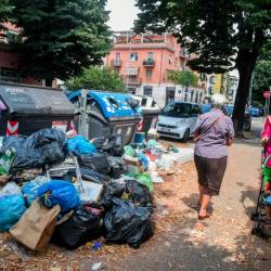 Residents walk past overflowing trash bins on July 10, 2019 in the Centocelle district of Rome. — AFP Relaxnews