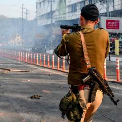 A security personnel fires tear gas during a curfew in Guwahati on Dec 12, following protests over the government's Citizenship Amendment Bill (CAB). — AFP