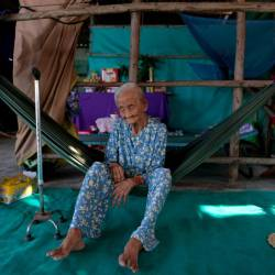 This photograph taken on April 21, 2019 shows 99-year-old Pham Thi Ca resting in a hammock in her makeshift shelter in Van Phong Bay. — AFP