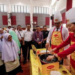 Students and officials look on as Education Ministry sports education and culture division deputy director Suhaimi Sun Abdullah (R2) and Maggi marketing manager Kimberly Oh (L) cook at the officiation of the 23rd Maggi Secondary Schools Cooking Competition 2019 at Sekolah Menengah Kebangsaan Agama Presint 11, Putrajaya on March 19, 2019. — Sunpix by Ashraf Shamsul