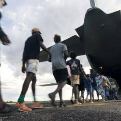 Residents of McArthur River, a remote town in the Northern Territory, boarding an Australian military plane as authorities evacuate communities in the path of a powerful cyclone. — AFP