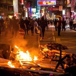 Protesters retreat from a burning barricade as police advance in the Mong Kok district in Hong Kong on Oct 20, 2019. — AFP