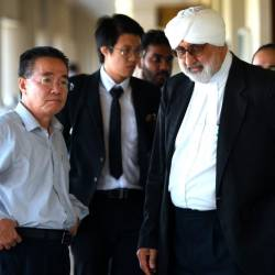 North Korean embassy counsellor Kim Yu Song (L) walks with Jagjit Singh (R), lawyer to Mun Chol Myong, the North Korean man facing extradition from Malaysia to the US on money-laundering, at the session court in Kuala Lumpur on Dec 13, 2019. — AFP