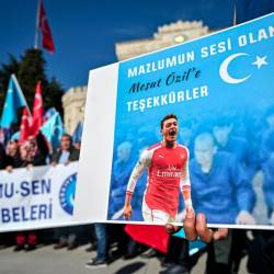 A supporter of China's Muslim Uighur minority holds a placard of Arsenal's Turkish origin German midfielder Mesut Ozil reading Thanks for being our voice past flags of East Turkestan during a demonstration at Beyazid square in Istanbul on Dec 14. — AFP