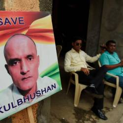 Indian residents sit next to a placard with the picture of Kulbhushan Jadhav, an Indian national convicted of spying in Pakistan, in the neighborhood where he grew up, in Mumbai. — AFP