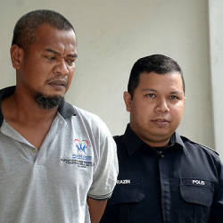A lorry driver, Mohammad Ridzuan Misropi, 41, (L) was brought to the Shah Alam magistrate's court today for allegedly causing the unintentional death of his wife at their home on Feb 7 this year. — Bernama