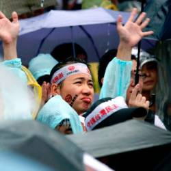 Protesters gather in the rain during a rally against pro-China media in front of the Presidential Office building in Taipei. — AFP