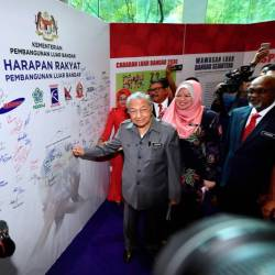 Prime Minister Tun Dr Mahathir Mohamad shows off the 'Harapan Rakyat' space that he signed, along with members of the public during the launch of the Rural Development policy at the Putrajaya International Convention Center (PICC) today. - Bernama
