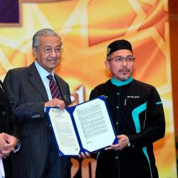 "File photo taken on Nov 19 shows Prime Minister Tun Dr Mahathir Mohamad recieving a memorandum from the President of the Islamic Preaching of Malaysia Foundation (Yadim) Nik Omar Nik Ab Aziz during the Closing Ceremony of the ""Multaqa Ulama Asia Tenggara 2019"" at Movenpick Hotel and Convention Centre. — Bernama"