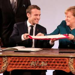 French President Emmanuel Macron and German Chancellor Angela Merkel exchange the French-German friendship treaty during the signing ceremony, on Jan 22, 2019 in the town hall of Aachen, western Germany. — AFP