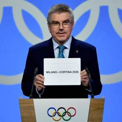 International Olympic Committee (IOC) president Thomas Bach shows the card with the name Milan/Cortina d'Ampezzo as the winning name of the 2026 Winter Olympics during the 134th session of the International Olympic Committee (IOC), in Lausanne on June 24, 2019. — AFP
