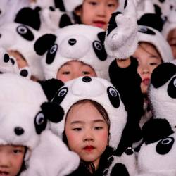 Children wearing a panda costume group together during the official reveal of the mascots for the Beijing 2022 Winter Olympic and Paralympic Games at Shougang Ice Hockey Arena, Shougang Park, Shijingshan District, Beijing in September 17, 2019. — AFP