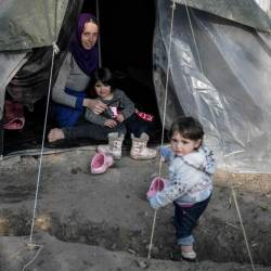 A syrian woman sits in her tent with her children in the Vial refugee camp, on the Greek island of Chios, on Dec 10. — AFP