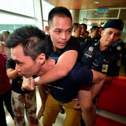 Mark Roger, 24, is carried by a friend on arrival at the Kuching International Airport on Feb 17, 2019. Roger, who has leg injuries, is among the 47 Malaysians who have returned after being detained in Poipet, Cambodia since Dec 11, 2018. — Bernama