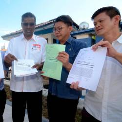 Penang DAP Law Bureau chief R.S.N. Rayer (C) and others show off the police report made against Bukit Gelugor Umno chief Datuk Omar Faudzar, at the Northeast district police headquarters in Jalan Patani, George Town today. - Bernama