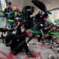 Protesters use a catapult against police during a protest Hong Kong's City University on Nov 12, following a day of pro-democracy protests. — AFP