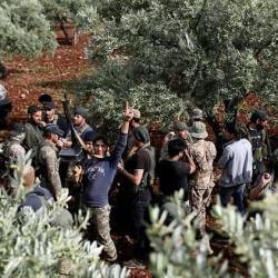 Syrian rebels gather in a field in the northern countryside of Hama province during clashes with regime forces. — AFP