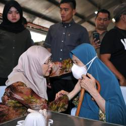 Deputy Prime Minister Datuk Seri Dr Wan Azizah Wan Ismail (seated left) helps fit the N95 face mask, on senior citizen Aishah Hussin (seated right), after handing out 1,200 N95 face masks to the public, courtesy of the Pandan Service Centre, at the Taman Nirwana Muhibah Complex, on Sept 21, 2019. — Bernama