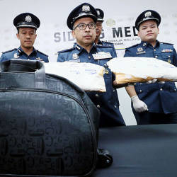 Kedah Customs director Datuk Johari Alifiah (C) and his officers display the methamphetamine drugs seized from a purported drug mule on the ICQS Complex walkway on Dec 16, 2018. — BBXpress