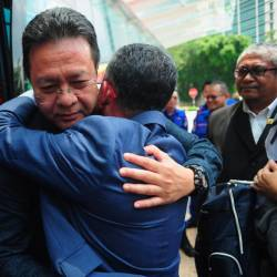 PKNS CEO Datuk Azizi Mohd Zain (R) hugs a survivor of the bus crash and PKNS staff member Bakhtiar Effendi Hamzah after arriving at the PKNS headquarters building in Section 14 today. - Bernama