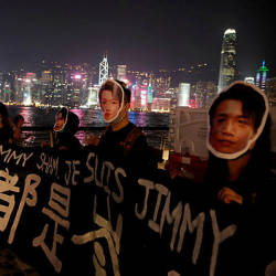 People wearing masks depicting Jimmy Sham hold a banner during an anti-government protest in Hong Kong, China, October 18, 2019. — Reuters