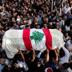 The coffin of slain Lebanese protester Alaa Abou Fakhr, draped in a national flag, is carried by mourners through the streets of his hometown of Chouaifet, southeast of Beirut, during his funeral procession on Nov 14. — AFP