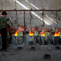 Ren Limin, a worker at the Jinyuan Company's smelting workshop, stokes the pots containing the rare earth metal Lanthanum before he pours it into a mould near the town of Damao, located in China's Inner Mongolia Autonomous Region Oct 31, 2010. — Reuters
