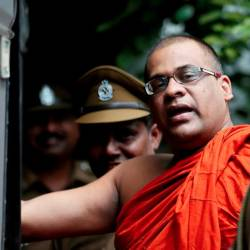 Galagoda Aththe Gnanasara Thero, head of Buddhist group Bodu Bala Sena (BBS), walks towards a prison bus while accompanied by prison officers after he was sentenced by a court in Sri Lanka on June 14, 2018. — Reuters