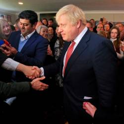Britain's Prime Minister Boris Johnson shakes hands with supporters during a visit to see newly elected Conservative party MP for Sedgefield, Paul Howell at Sedgefield Cricket Club in County Durham, north east England on December 14, 2019, following his Conservative party's general election victory. - Reuters