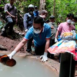 A Health Ministry staff collects a water sample from a hill water catchment area leading towards the Pertang River at Kampung Kuala Koh on June 26, 2019. — BBX