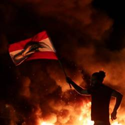 A Lebanese anti-government protester carries a Lebanese flag as he runs in front of burning tires blocking the main highway linking the city of Tripoli to Beirut at the coastal city of Byblos, north of the capital on Nov 13. — AFP