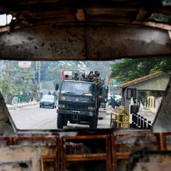 Soldiers are seen through the wreckage of a vehicle which was set on fire by demonstrators during a protest against the government's Citizenship Amendment Bill (CAB) in Guwahati on December 13, 2019. - AFP